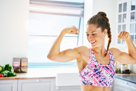 Laughing sportive girl showing biceps at kitchen