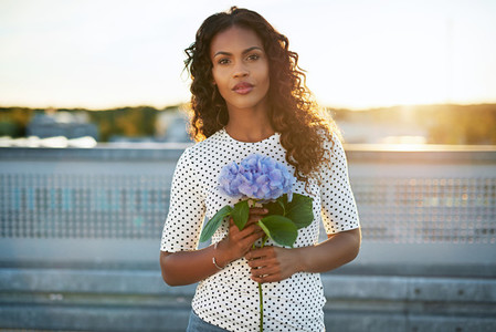 Pretty afro american woman holding a flower