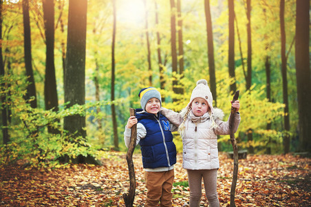 Two kids holding branches in autumn forest