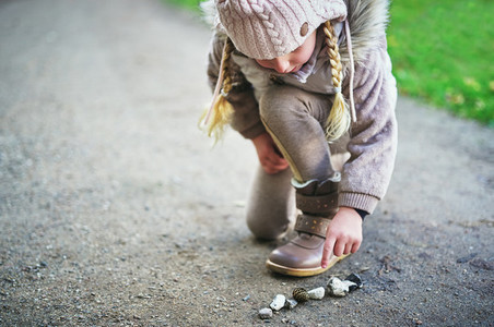 Little girl touches stones on a road