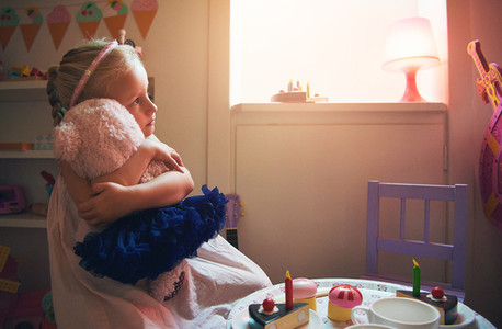 Cute girl embracing toy bear while tea party