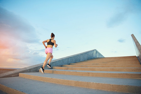 Fit healthy young woman jogging up stairs