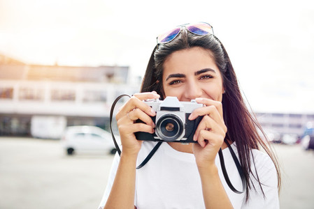 Smiling happy female tourist with a camera
