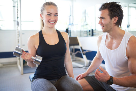 Gym Trainer Assisting Female in Lifting Weights