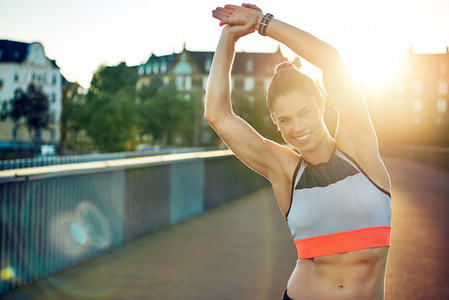 Female athlete smiles at camera and stretches