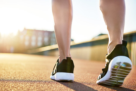 Bare legs in running shoes preparing to exercise