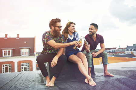Cheerful group of barefoot adults drinking beer