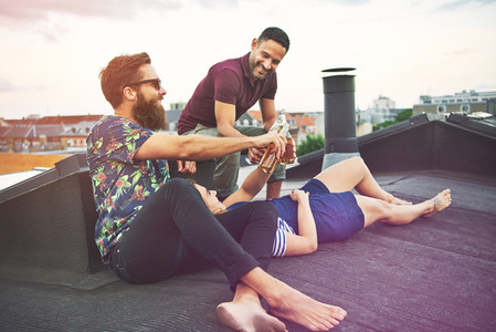 Woman in lap of bearded man drinking with friend