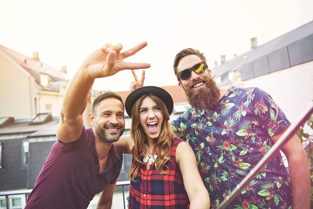 Man makes peace sign beside two smiling friends