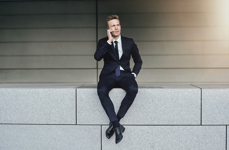 A businessman with legs crossed speaks phone