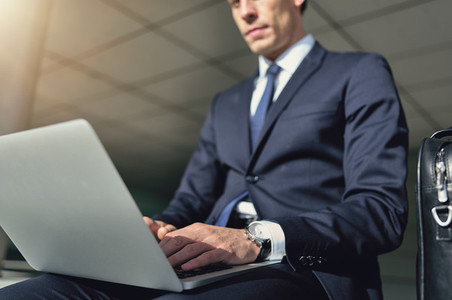 Confident businessman works with his gray notebook