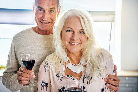 Close up on cheerful middle aged couple with wine