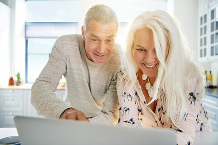 Excited senior couple looking at a laptop together