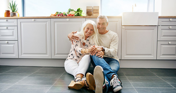 Happy couple sitting on kitchen floor