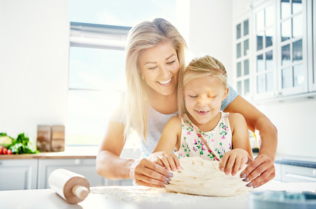 Pretty little girl kneading dough with her mother