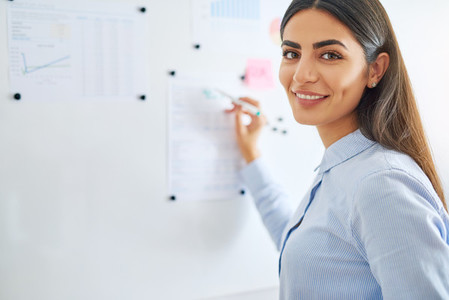 Happy business woman writing on white board