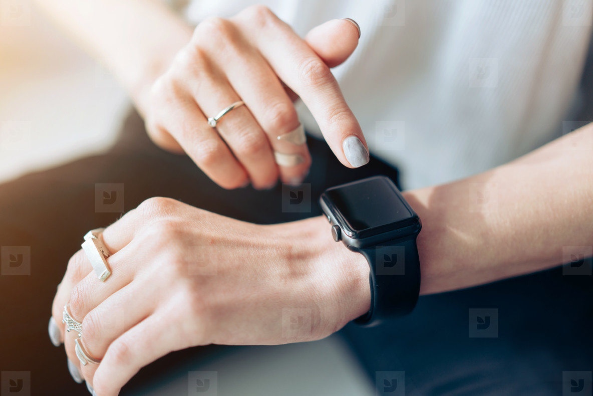Womans hand touching the screen of a smart watch