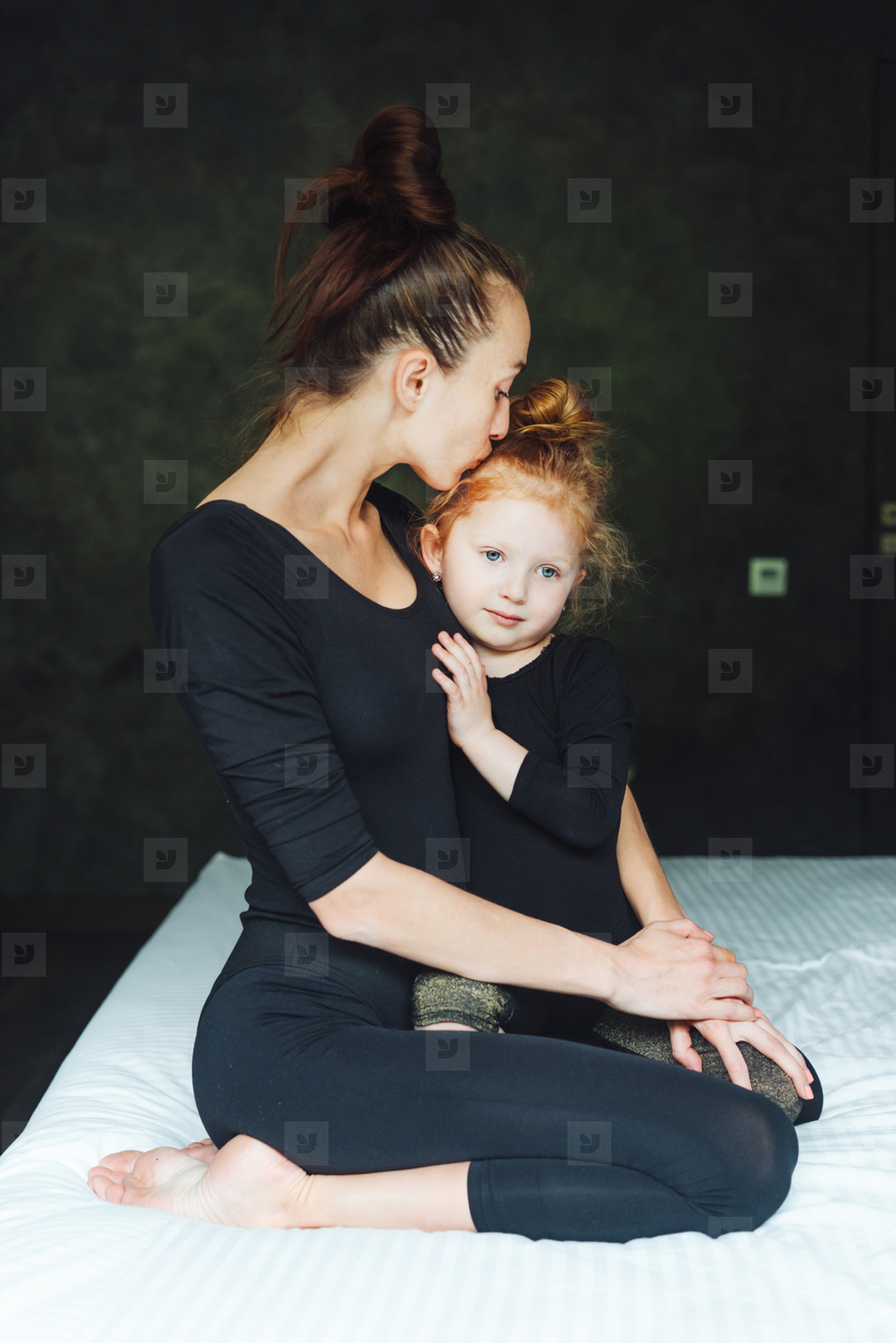 Mom and daughter have fun on the bed