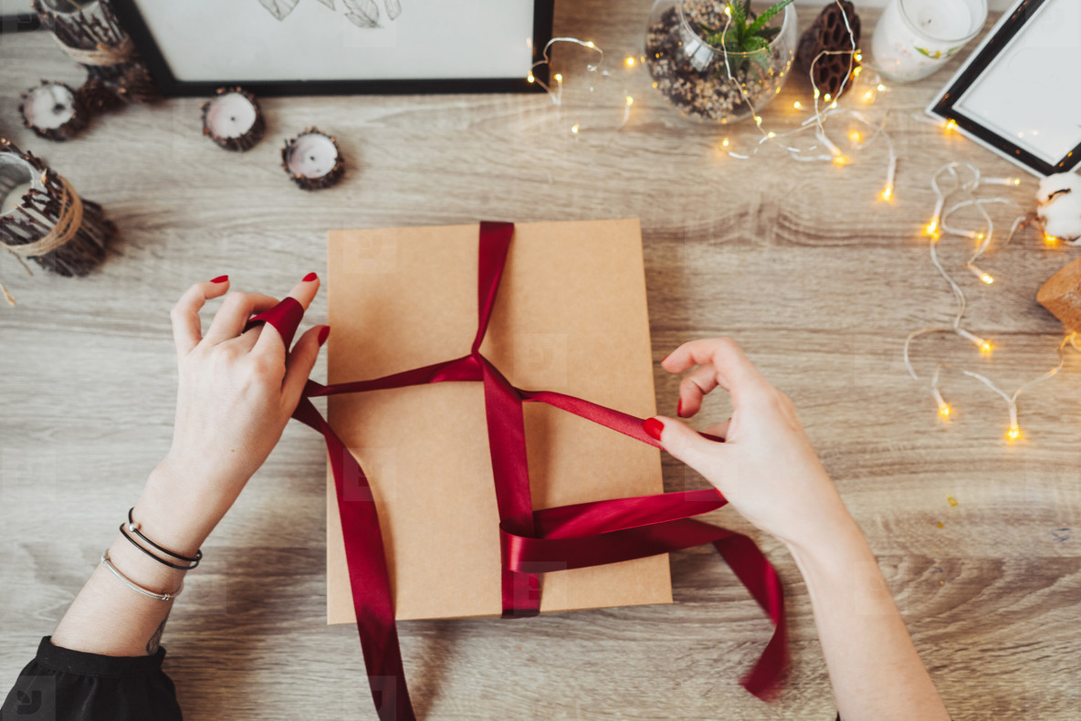 Woman wrapping present in paper with red ribbon