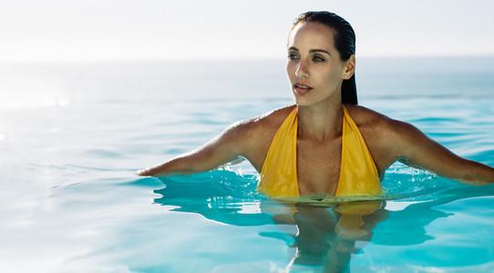 Woman swimming in an infinity pool