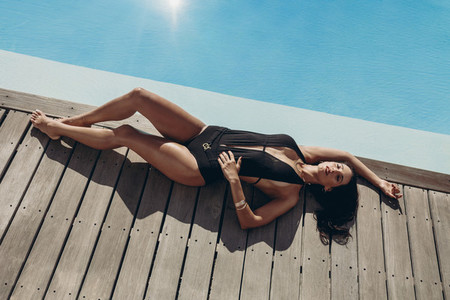 Attractive woman tanning at the swimming pool