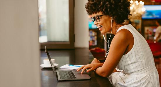 Smiling woman sitting at cafe using laptop