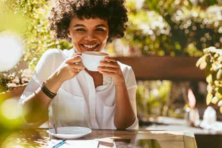 Cheerful african woman having coffee