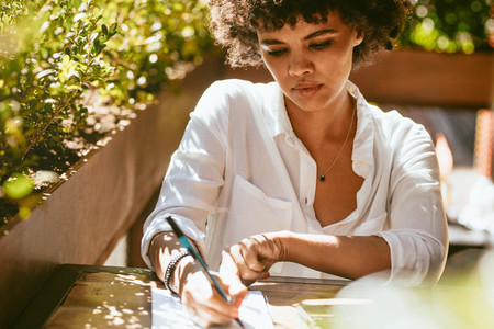 African female at cafe writing notes
