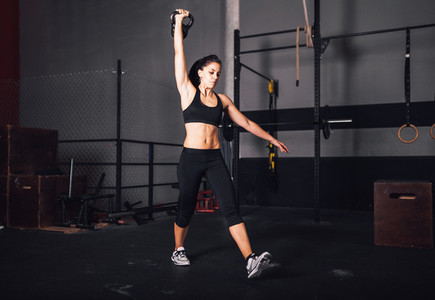 Young woman realizing indoor exercises with kettlebell