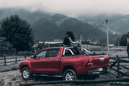 the girls get on the car and look at the mountains