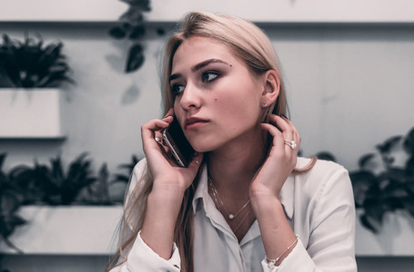 cute blonde woman speaks on the phone indoors cafe