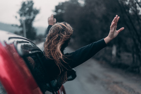 the girl raised her hands up from the car window and rides along the road against the background of the mountains