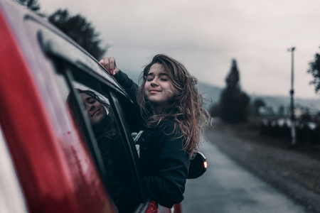 cute girl leaning out of an open car window enjoy and smiling with outstretched arms  Concept travel like a lifestyle