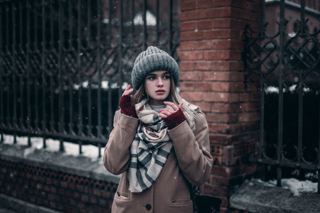 girl in gloves and a warm hat looks out onto the street