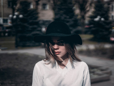 Girl in a hat walks on sunny day