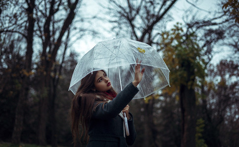 girl holding a transparent umbrella in an autumn park