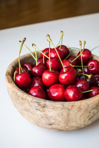 Red cherries in wooden bowl
