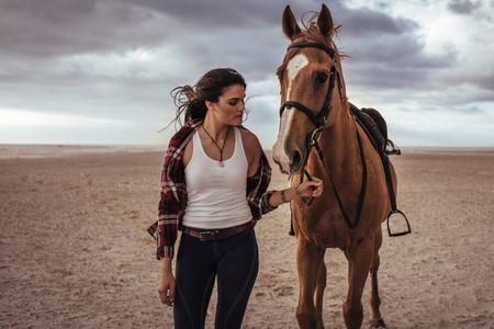Equestrian walking with a stallion in evening