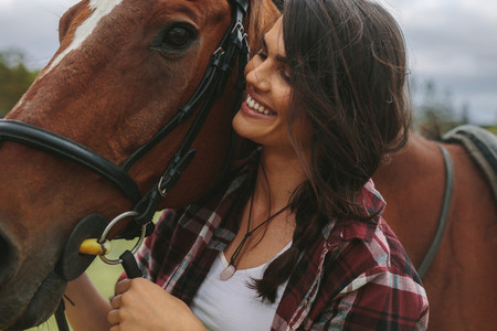 Smiling cowgirl with her horse