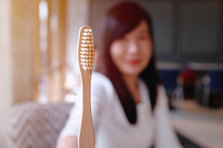Asian woman showing wooden bamboo toothbrush