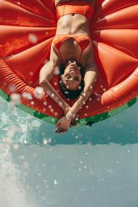 Woman sunbathing on inflatable mattress in pool