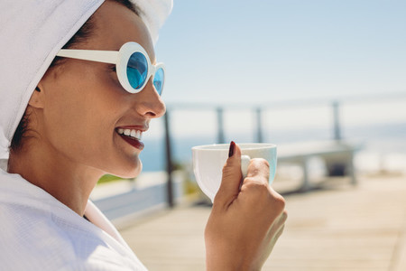 Woman in bathrobe having coffee