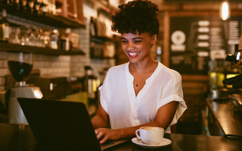 Smiling coffeeshop owner using laptop