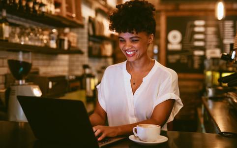 Smiling coffeeshop owner using laptop