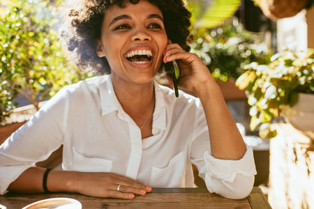 Woman smiling and talking on phone at a cafe