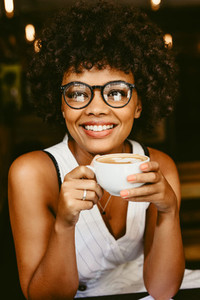 African female having coffee at cafe