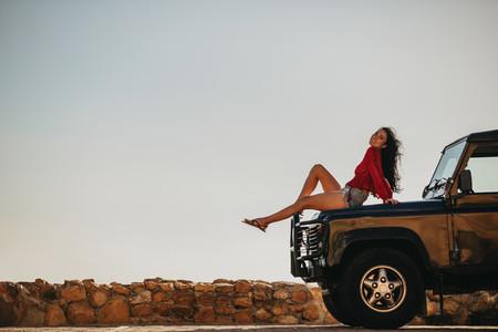 Beautiful woman sitting on car hood