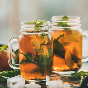 Summer refreshing cold peach ice tea on tray with ice
