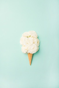 Waffle cone with white flowers over blue background top view