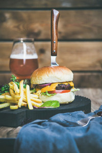 Classic burger dinner with glass of beer and french fries